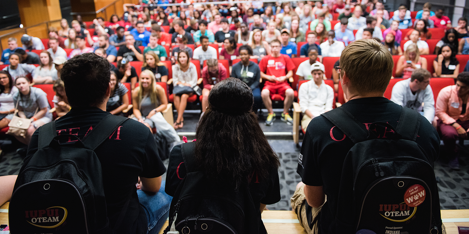 A photo of oteam members sitting in front of students at orientation.