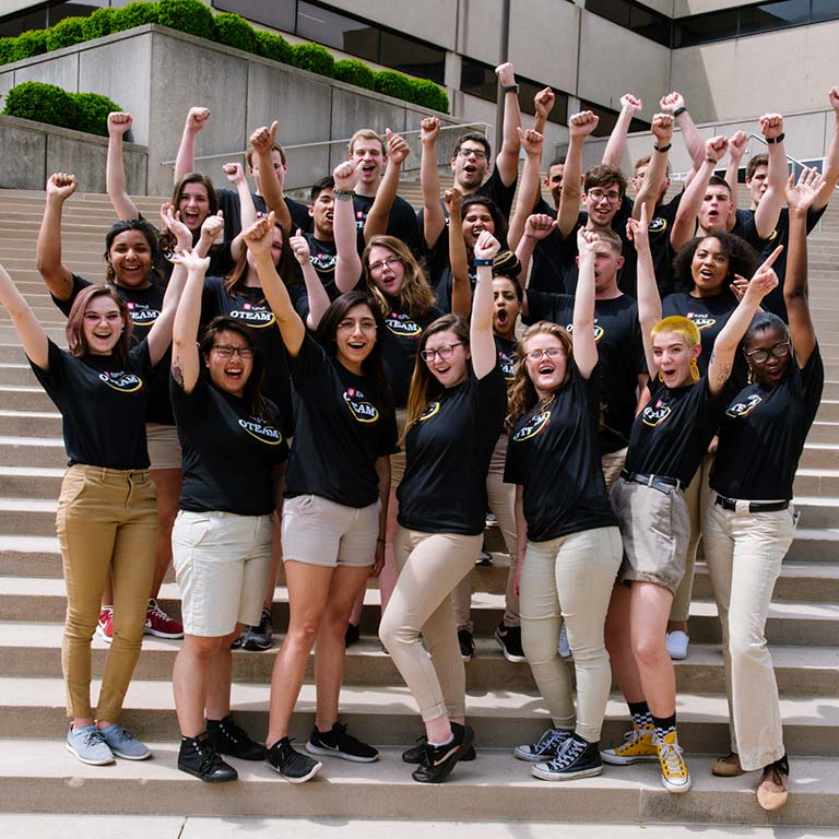 A group of OTEAM leaders cheer with their hands in the air on the steps of the library.