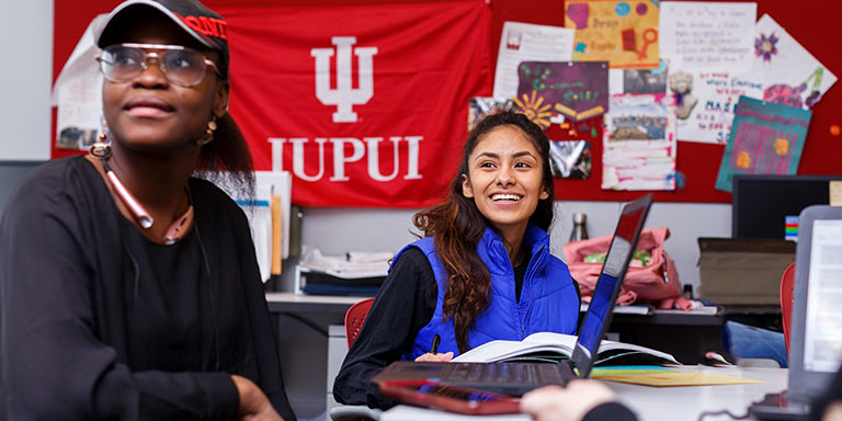 Two girls look past the camera smiling, while sitting at a table with an IUPUI flag hung on the wall behind them.